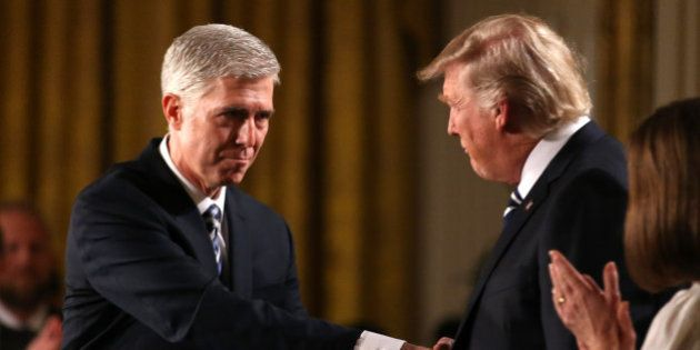 Judge Neil Gorsuch (L) shakes hands with U.S. President Donald Trump as Gorsuch's wife Louise (R) applauds...