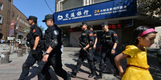 Chinese armed police patrol the streets of the Muslim Uighur quarter in Urumqi after a series of recent...