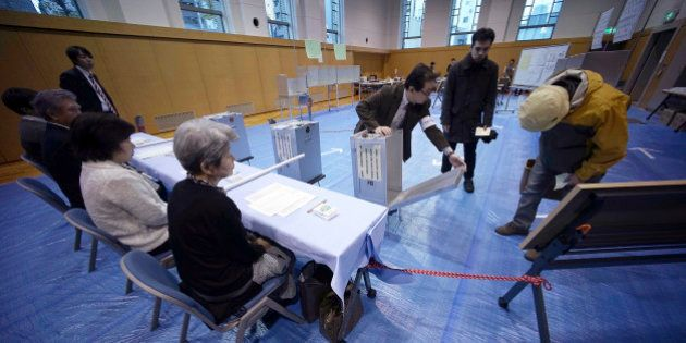 A representative of a local election administration commission shows the earliest two voters the empty...