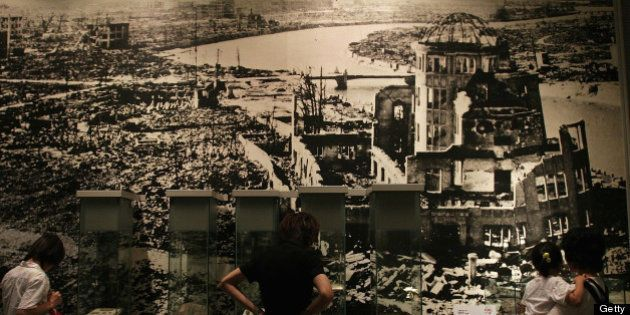 HIROSHIMA, JAPAN - JULY 27: Visitors look at a picture, showing the aftermath of the atomic bomb attack,...