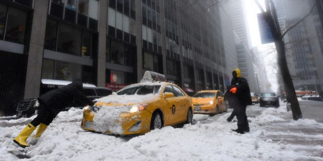 Men try to push a cab stuck in the snow on a street in New York on March 14, 2017.Winter Storm Stella...