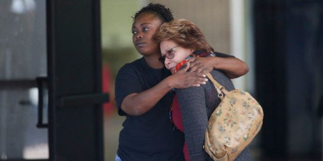 Two women embrace at a community center where family members are gathering to pick up survivors after...