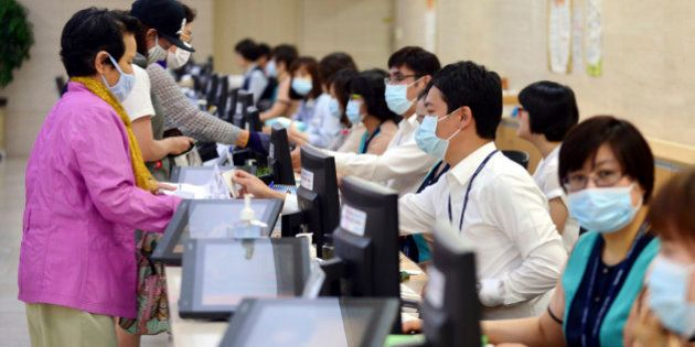 Hospital workers, right, wear masks as a precaution against Middle East Respiratory Syndrome virus as...