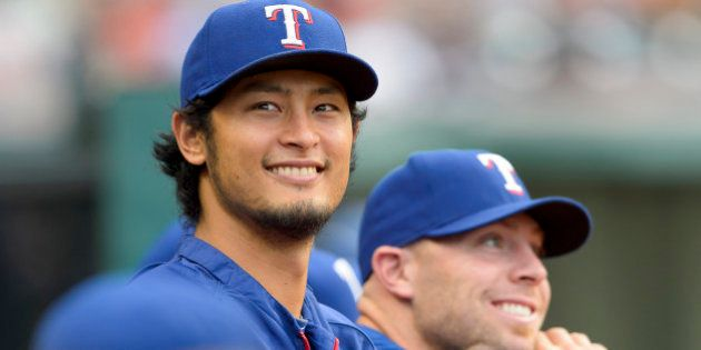 CLEVELAND, OH - AUGUST 1: Pitcher Yu Darvish #11 of the Texas Rangers watches the game from the dugout...