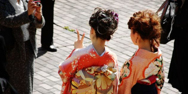 Two Japanese girls on their university graduation day. Thay are dressed to kimonos and hakama