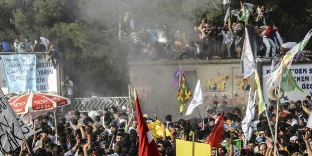 People look at smoke from an explosion which injured several people during a rally by the pro-Kurdish...