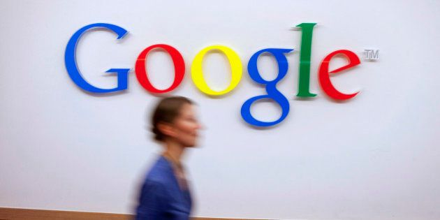 A Google Inc. employee walks past a logo outside the entrance to the company's offices in Berlin, Germany,...