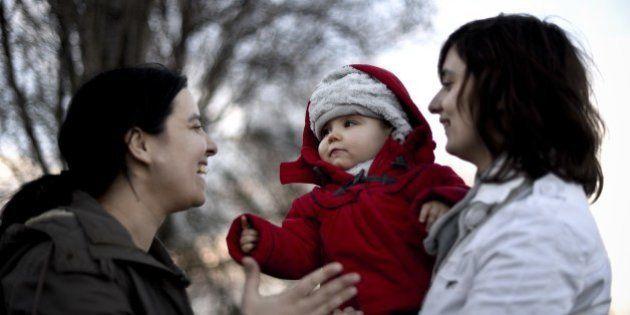 Same sex couple Olga Miranda (R) and Matilde Custodio (L) hold their daughter Carolina during a walk...