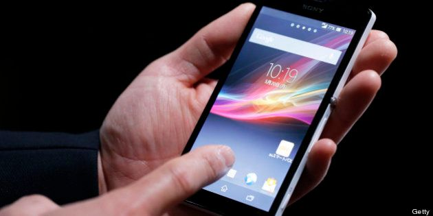 An employee demonstrates KDDI Corp.'s au brand Xperia UL SOL22 smartphone, manufactured by Sony Mobile...