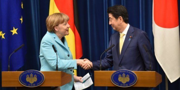 German Chancellor Angela Merkel (L) and Japanese Prime Minister Shinzo Abe (R) shake hands after their...