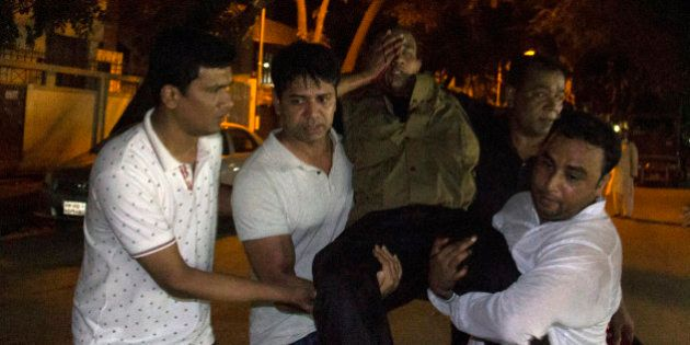 People carry an injured man near the Holey Artisan Bakery restaurant during an attack by unidentified...