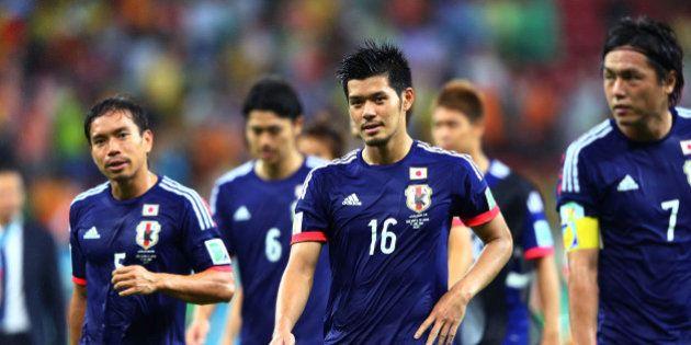 RECIFE, BRAZIL - JUNE 14: Yuto Nagatomo (L) and Hotaru Yamaguchi of Japan walk off the field with teammates...
