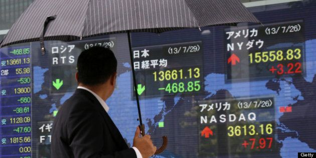 A pedestrian holding an umbrella looks at an electronic stock board displaying the closing figure of...