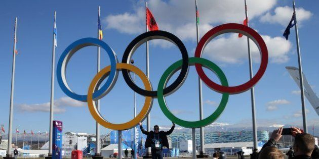 People pose with the Olympic rings inside Olympic Park at the Winter Olympics in Sochi, Russia, Thursday,...