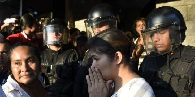 Relatives gather outside the children's shelter Virgen de la Asuncion after a fire at the facility killed...