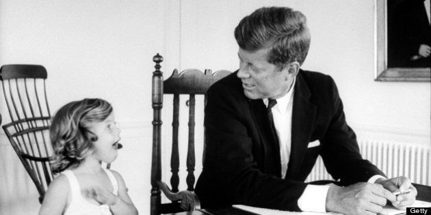 Sen. John Kennedy chatting w. his young daughter Caroline as he goes over some papers on table at his...