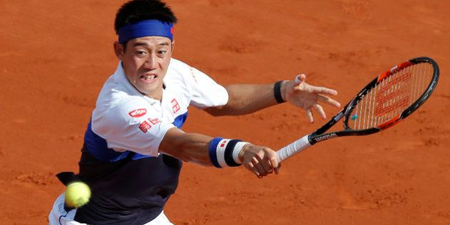 Japan's Kei Nishikori returns the ball to France's Jo-Wilfried Tsonga during their quarterfinal match...