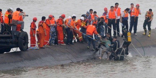 A survivor (C) is rescued by divers from the Dongfangzhixing or 'Eastern Star' vessel which sank in the...