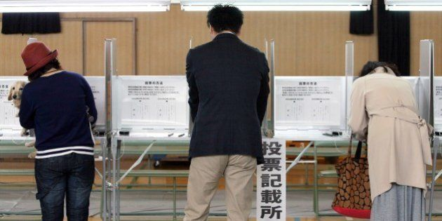 Voters fill in ballot papers at a polling station in Osaka on May 17, 2015 to vote on a referendum to...