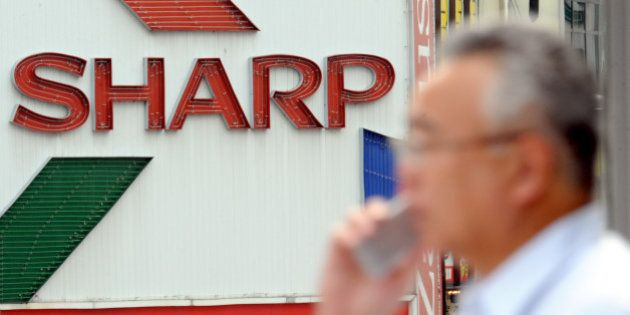 A man speaking on a mobile phone walks by a billboard of Sharp Corp. in Tokyo Thursday, July 31, 2008....