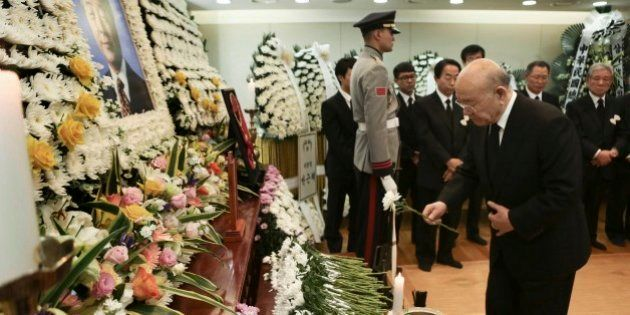 Former South Korean President Chun Doo-hwan, right, places a flower at a memorial altar for the late...