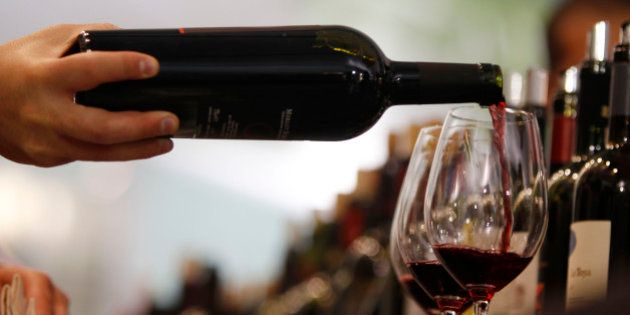 A man pours a glass of red wine on the opening day of the 44th edition of the annual International Wine...