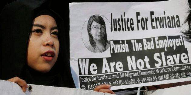 A supporter of Indonesian maid Erwiana Sulistyaningsih, holds a placard as Sulistyaningsih arrives at...