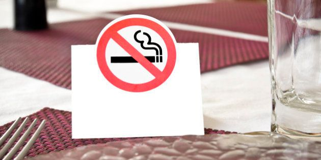 Close up of white no smoking sign displayed on a table in a public establishment (restaurant for example)...