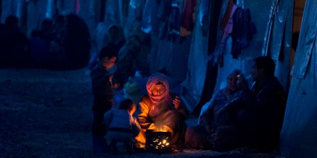 An elderly Syrian Kurdish refugee woman from the Kobani area, warms up by a fire at a camp in Suruc,...