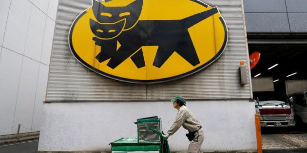 A deliverer of Yamato Transport Co is seen under the company's logo at a business district in Tokyo,...