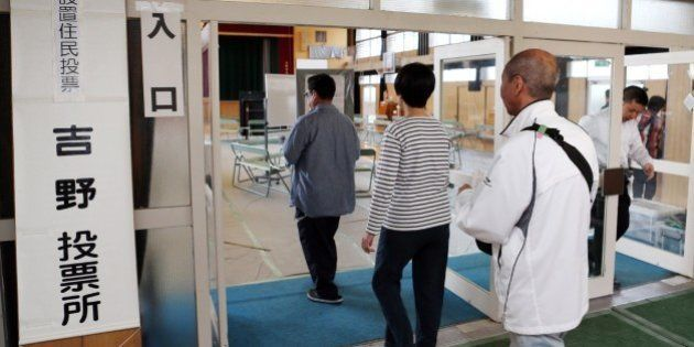 Residents enter a polling station in Osaka on May 17, 2015 to voite on a referendum to reform the city...