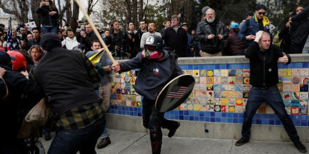 A demonstrator in support of U.S. President Donald Trump swings a stick towards a group of counter-protesters...