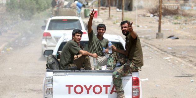 Iraqi government forces flash the 'V' for victory sign in Fallujah, 50 kilometres (30 miles) from the...