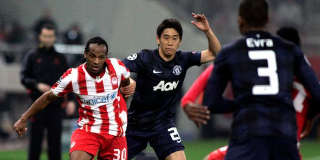 PIRAEUS, GREECE - FEBRUARY 25: Olympiakos' Leonardo Salino holds off the challenge of Shinji Kagawa of...