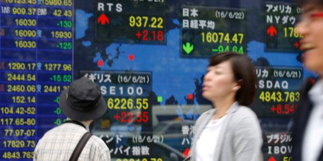 A man looks at an electronic stock indicator of a securities firm in Tokyo, Wednesday, June 22, 2016....