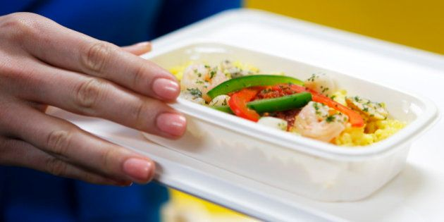 A cabin attendant displays an in-flight meal of paella-style rice for Vanilla Air during a media preview...