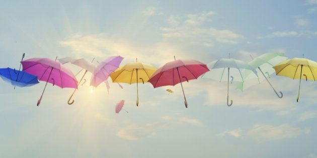 Conceptual photo of different color umbrellas lined-up across the sky. Sun is behind them shining, and...