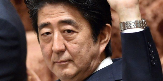 Japanese Prime Minister Shinzo Abe raises his hand to answer questions during the Lower House's ad hoc...
