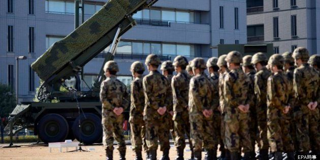 Japanese military personel stand in front of Patriot Advanced Capability (PAC-3) surface-to-air missile...