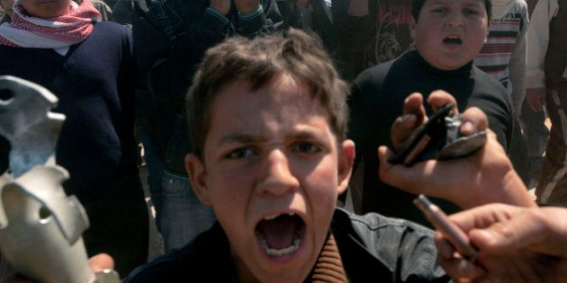 Syrians carry the coffin of 13-year-old Ahmad bin Muhsin Qarush during his funeral on March 24, 2012...