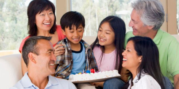 Family in living room with cake