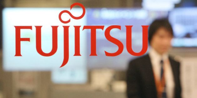JAPAN - DECEMBER 04: An employee walks behind the logo for Fujitsu Ltd. at the company's offices in Tokyo,...