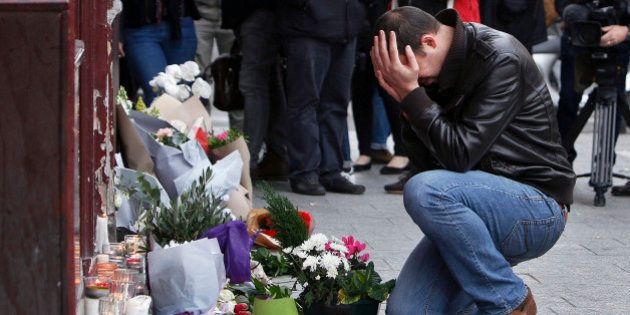 A man holds his head in his hands as he lays flowers in front of the Carillon cafe, in Paris, Saturday,...