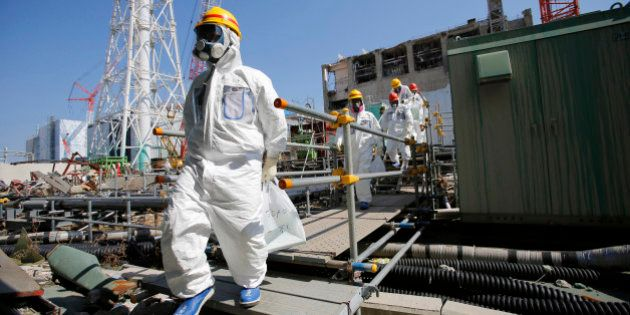 Members of the media and Tokyo Electric Power Co. (Tepco) employees, wearing protective suits and masks,...
