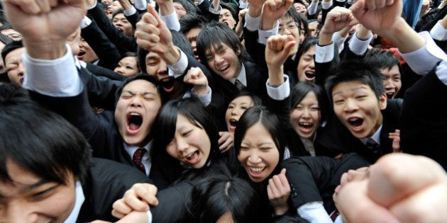 College students raise their arms and shout at the start of a job hunting ceremony in Tokyo on February...