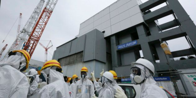 Members of the media and Tokyo Electric Power Co. (Tepco) employees wearing protective suits and masks...