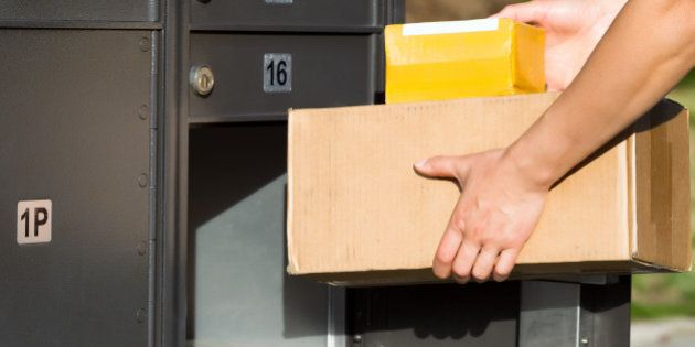 Horizontal image of female hands putting packages into postal mailbox with green grass and sidewalk in