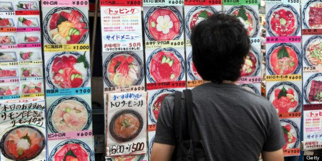 A man looks at menu items displayed outside a Japanese restaurant in Tokyo, Japan, on Monday, June 25,...