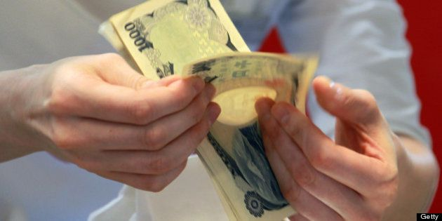 A salesclerk counts Japanese yen bank notes in the newly opened Lumine Co. shopping complex in the Yurakucho...