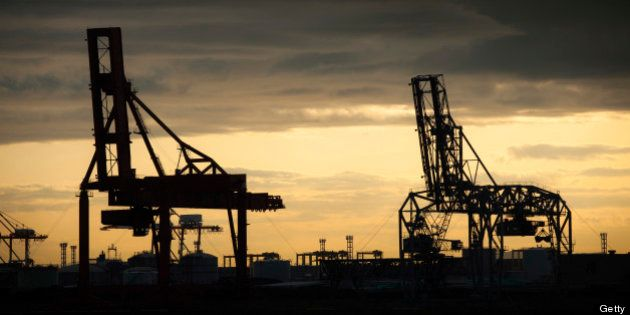 Cargo cranes are silhouetted against a golden sky at the Osaka harbor and shipping complex in